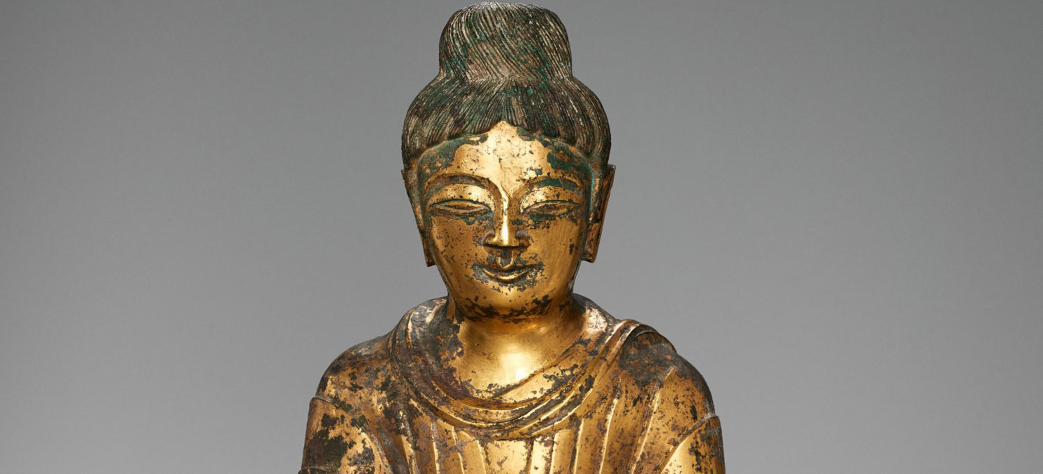 Face and shoulders of a golden Buddha statue.