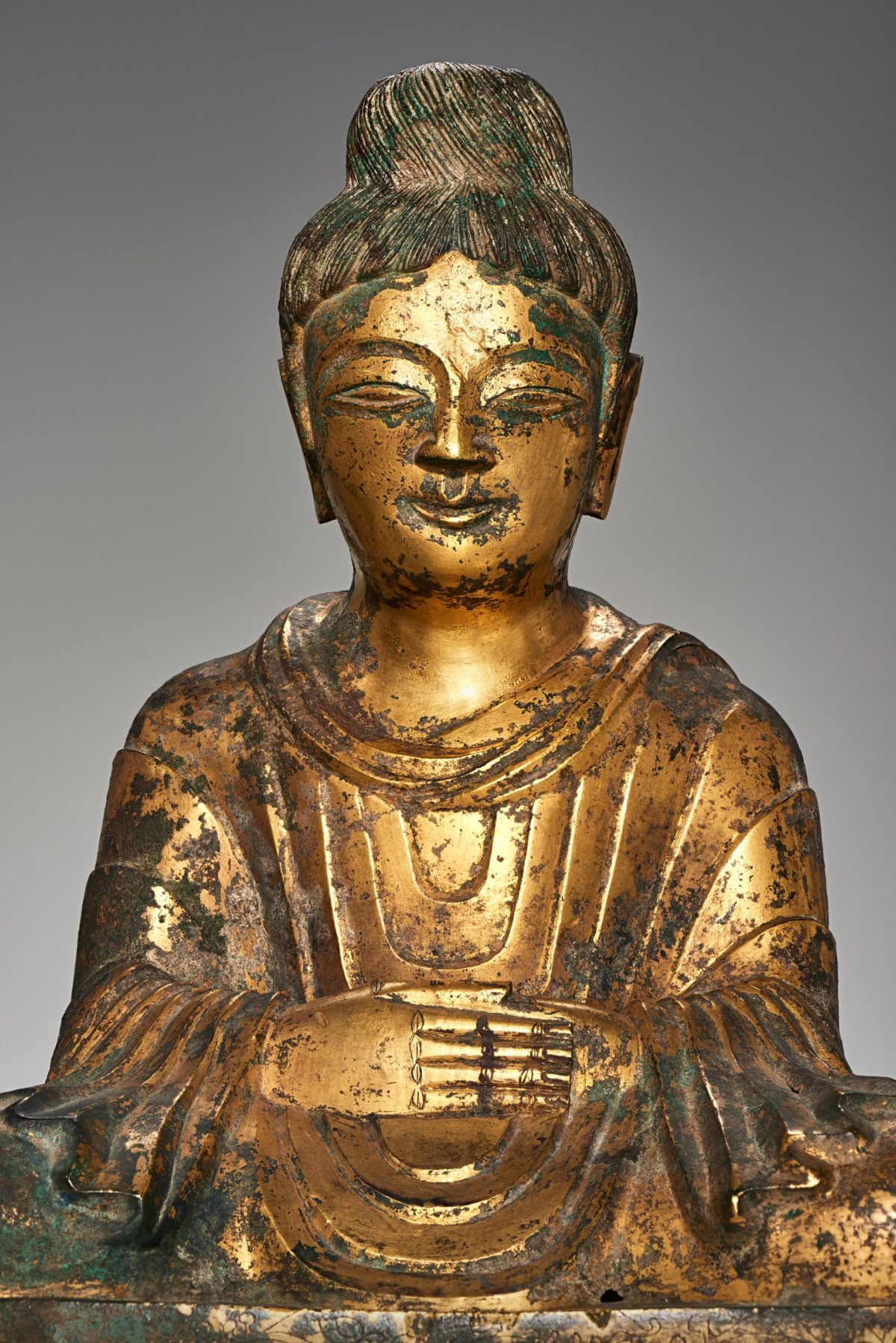 Face and shoulders, and body of a golden Buddha statue.