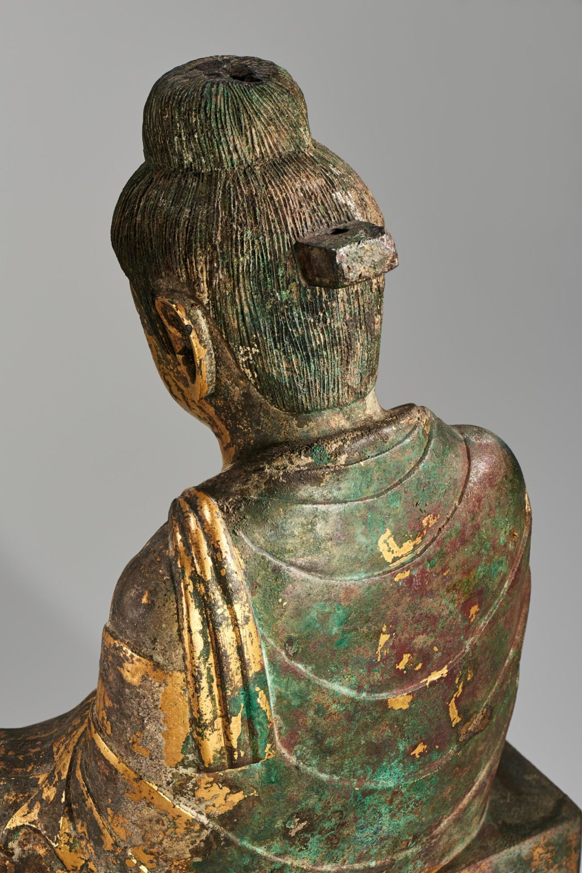 Close up view of the back of the head of a golden Buddha statue.