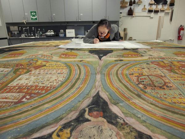 A conservator works on restoring a large artwork
