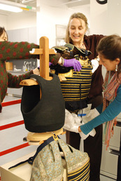 Conservators work on a suit of Japanese armor.